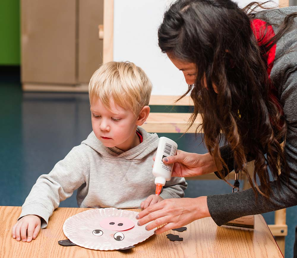 Little boy working on a craft with his teacher