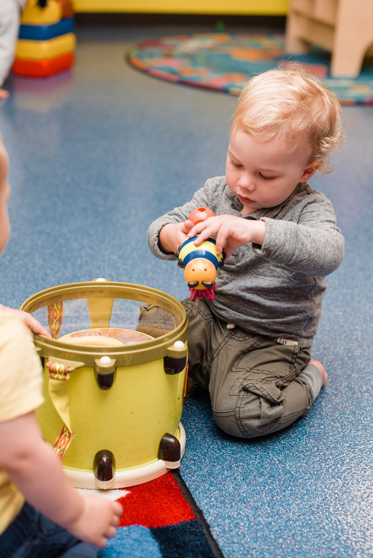 Toddler playing with toy in playroom